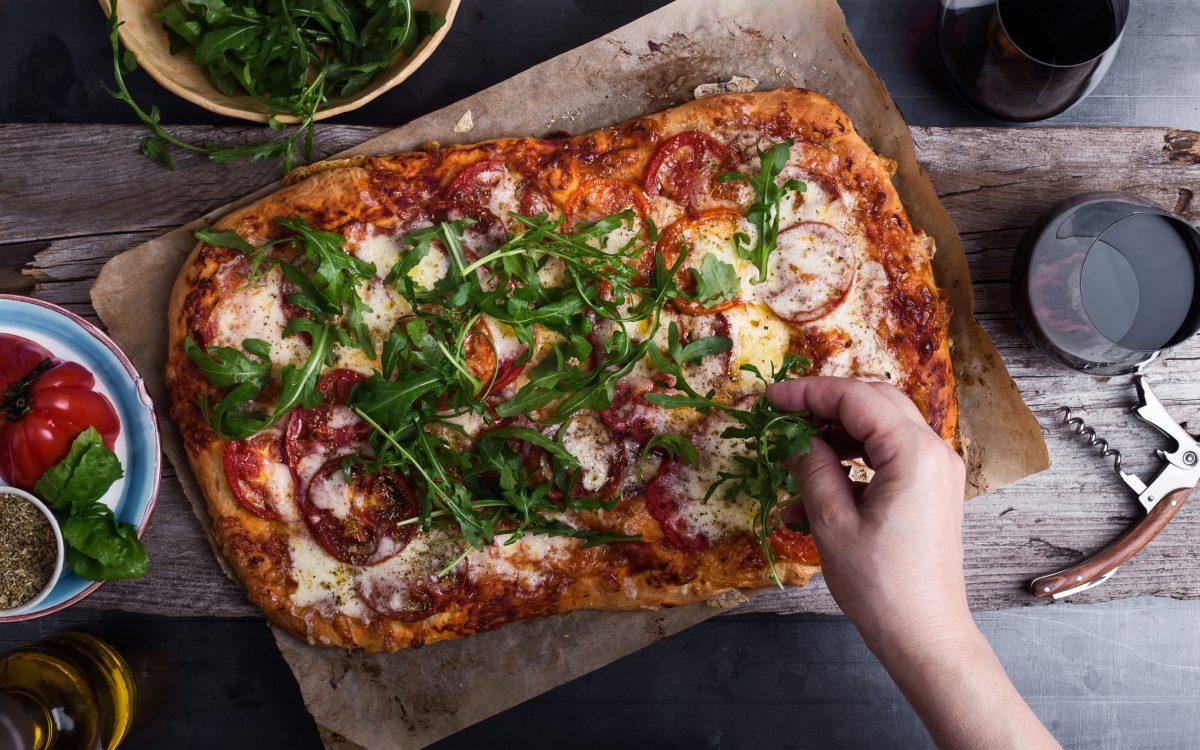 Gebackene Pizza wird mit Rucola belegt