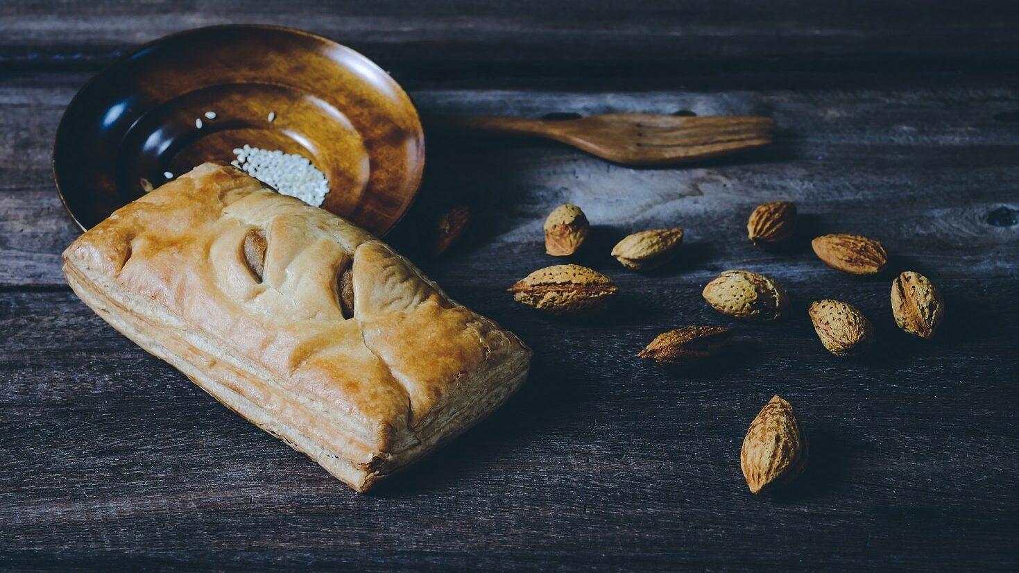 Eine Apfeltasche liegt auf einer Holzplatte. Daneben befinden sich ein paar Nüsse.