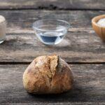 Die wichtigsten Zutaten für die Autolyse: Mehl und Wasser in Schalen neben einem angerührten Autolyseteig im Hintergrund mit einem Laib Brot im Vordergrund auf einem Holztisch.