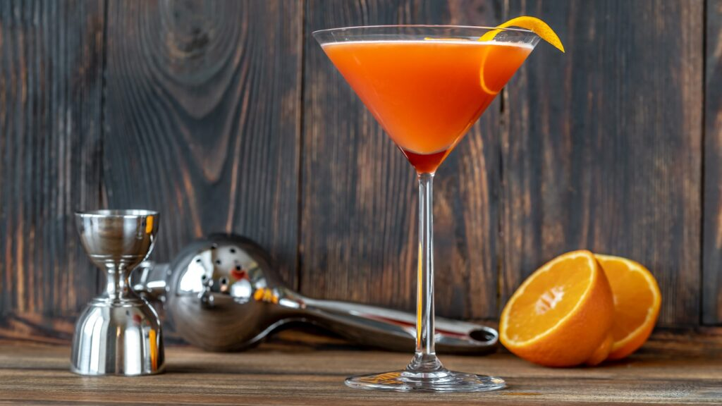 Der Blood and Sand-Cocktail eingegossen in einem Martini-Glas. Im Hintergrund liegt eine aufgeschnitte Orange sowie eine Presse und ein Messbecher.