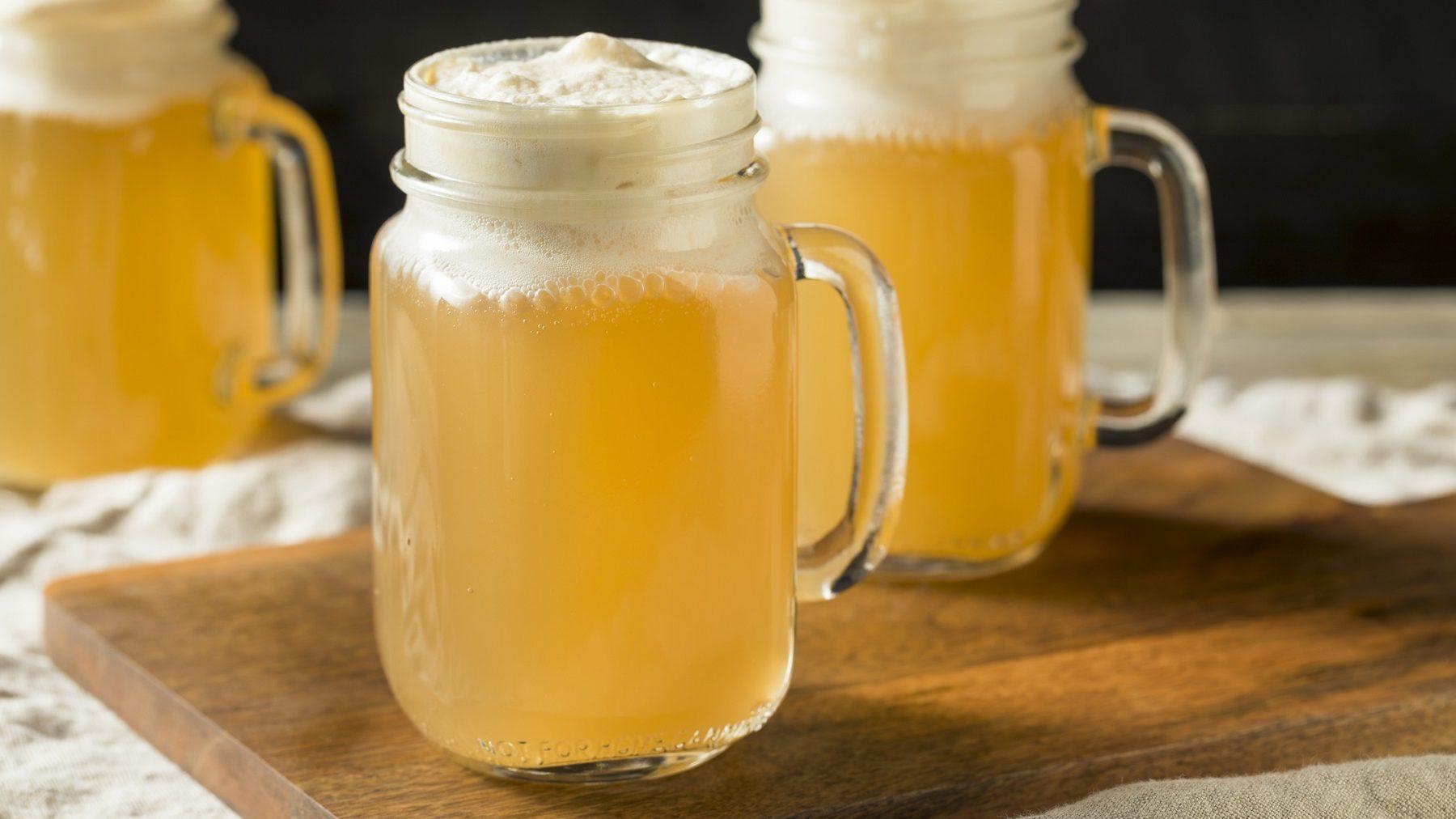Zwei gläserne Krüge mit Butter-Bier stehen auf einem Holzbrett auf einem Tisch mit einer beigen Tischdecke. Im Hintergrund steht ein weiteres Butter-Bier. Die Biere sind angerichtet mit Sahne.
