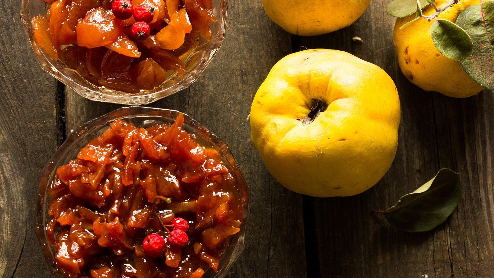 Chutney mit Quitten und Äpfeln in zwei Glasschüsseln angerichtet neben frischen Quitten vor einem Holz-Hintergrund von oben.