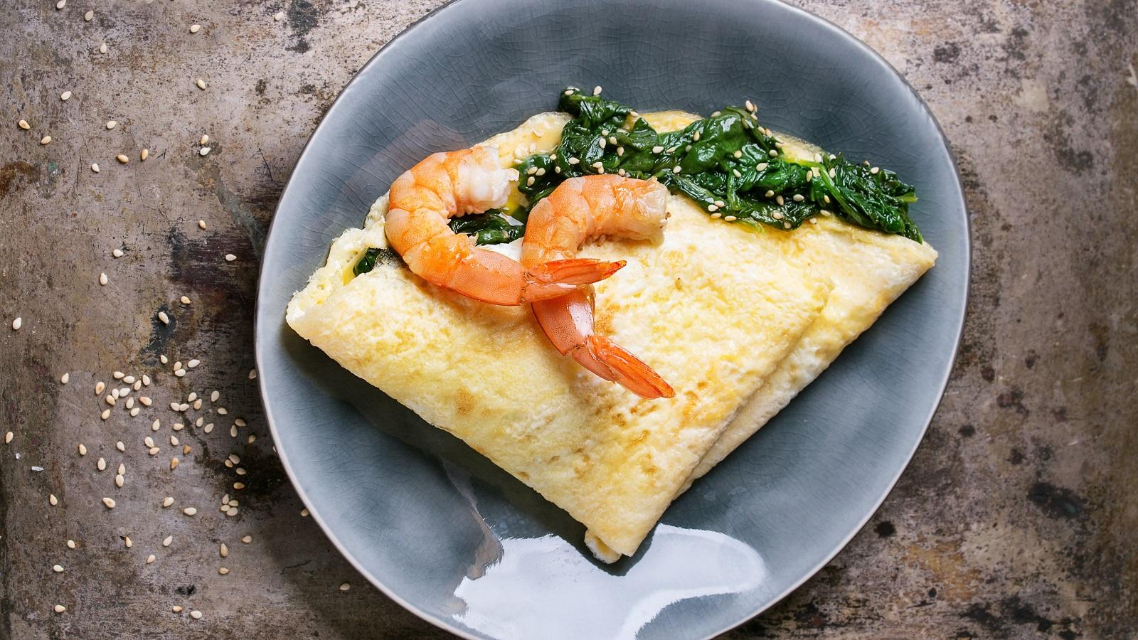 auf einem Tisch steht ein Teller mit einem Omelett. Das ist mit Spinat gefüllt und und geviertelt. Obenauf liegen zwei Garnelen.