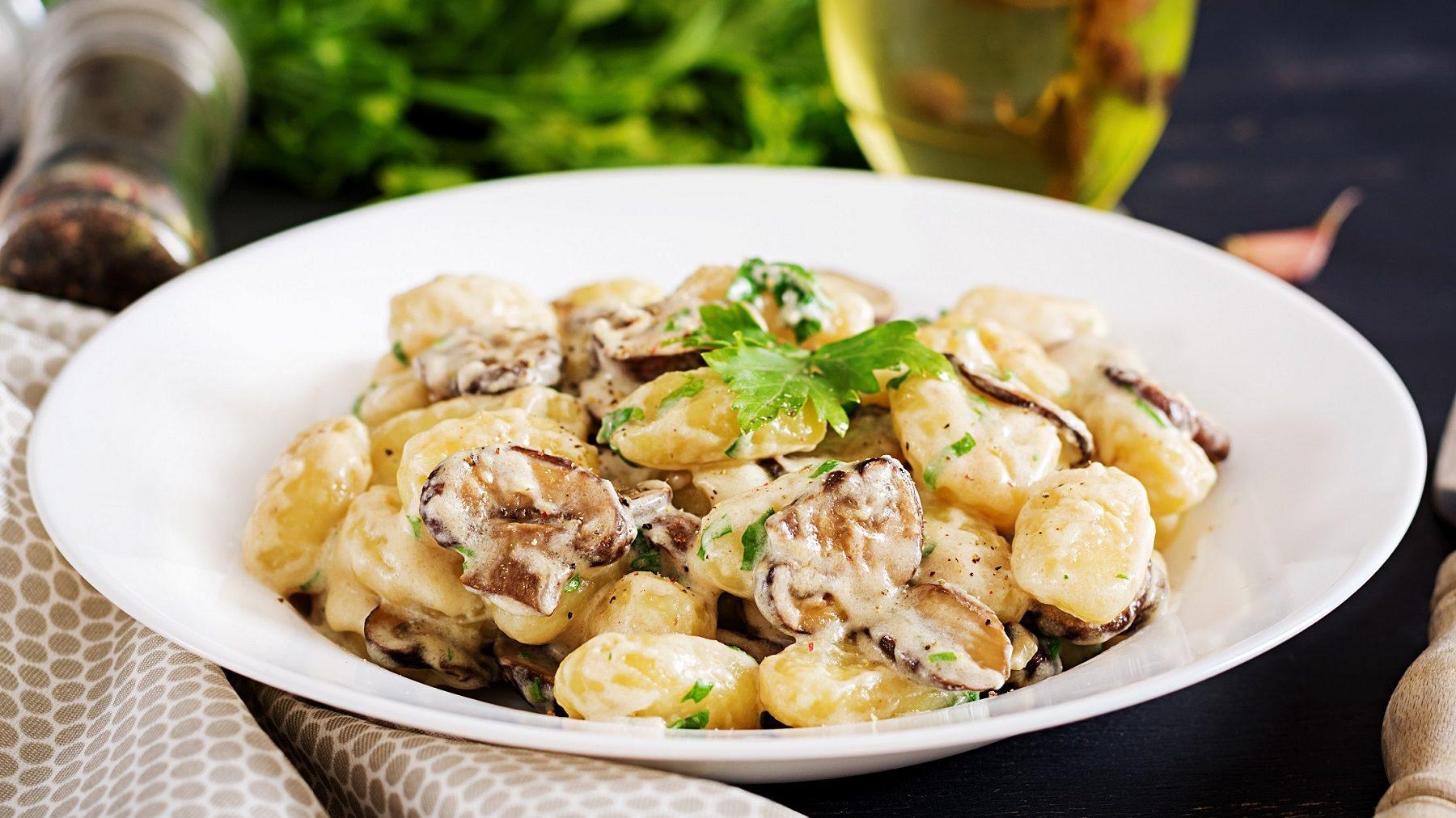 Auf dem Bild ist ein weißer Teller mit Gnocchi in Pilz-Käse-Soße.