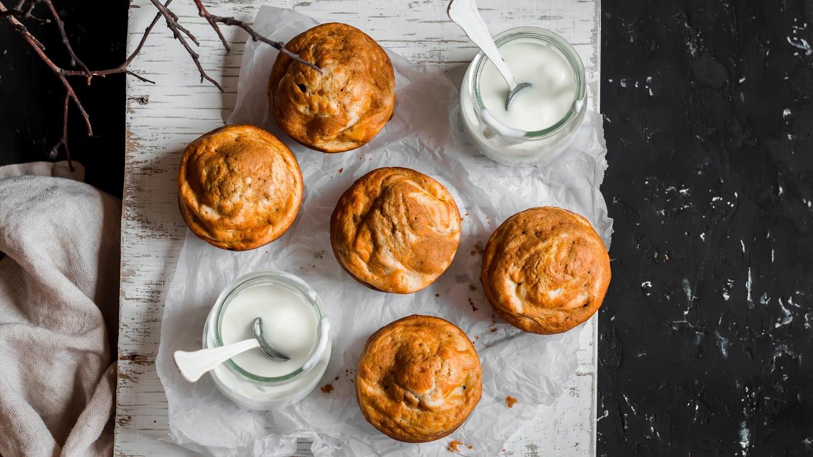 Fünf Kürbis-Frischkäse-Muffins auf einem weißen Backpapier zusammen mit zwei Gläsern Frischkäse angeordnet, vor einem schwar-weißen Hintergrund, von oben.
