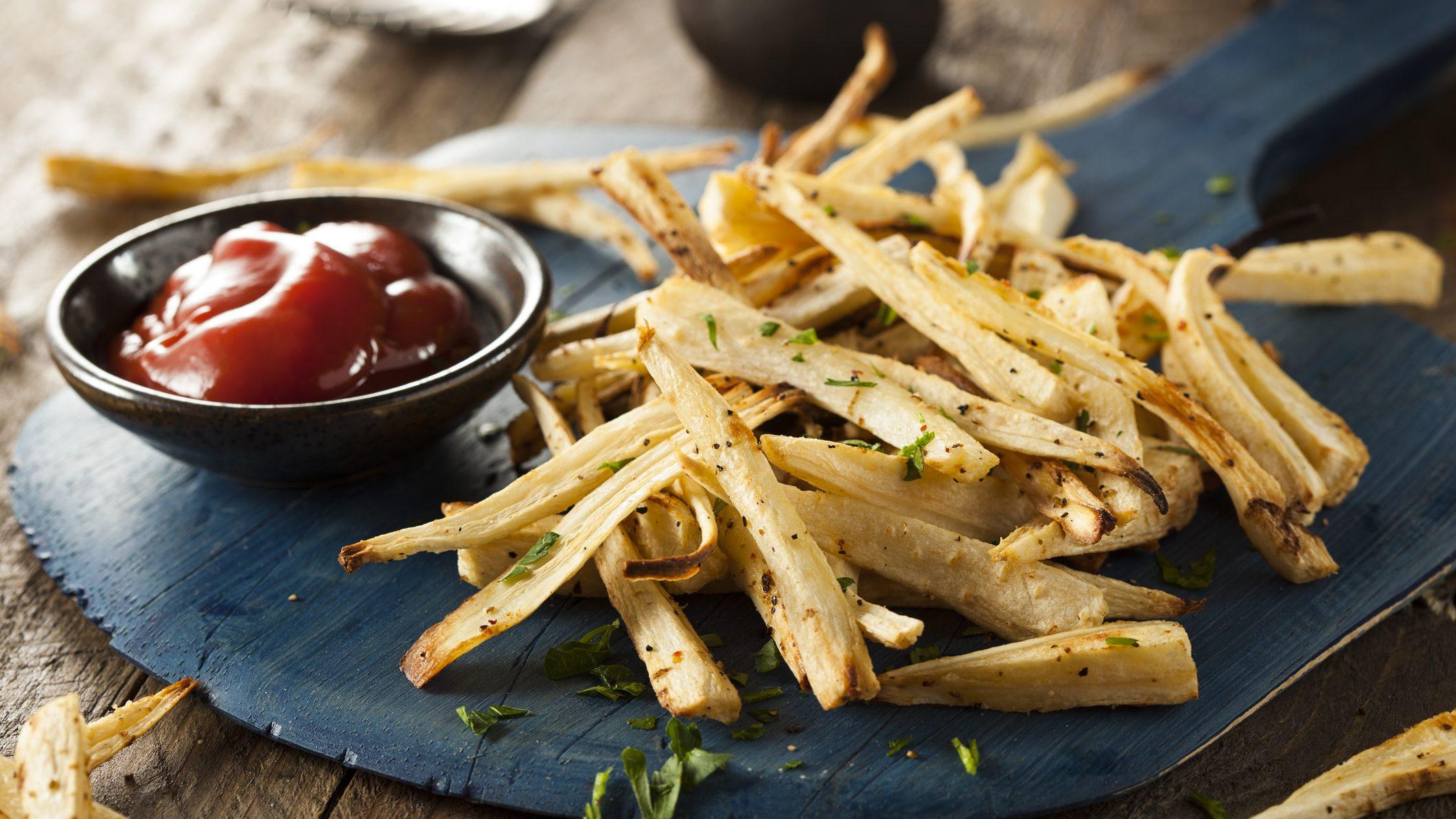 auf einem dunklen Holzbrett liegen Pommes aus Petersilienwurzeln. Danebenn stehte eine kleine Schale mit Ketchup