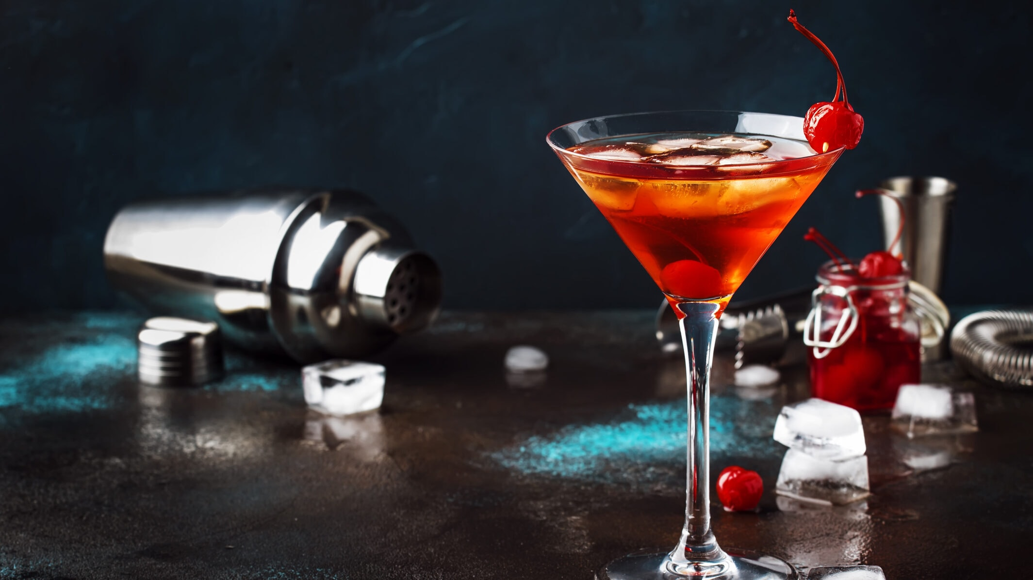 Ein Manhattan in einem Martiniglas, dekoriert mit einer Cocktailkirsche. Im Hintergrund ein umgekippter Cocktail-Shaker und verstreut die Zutaten.