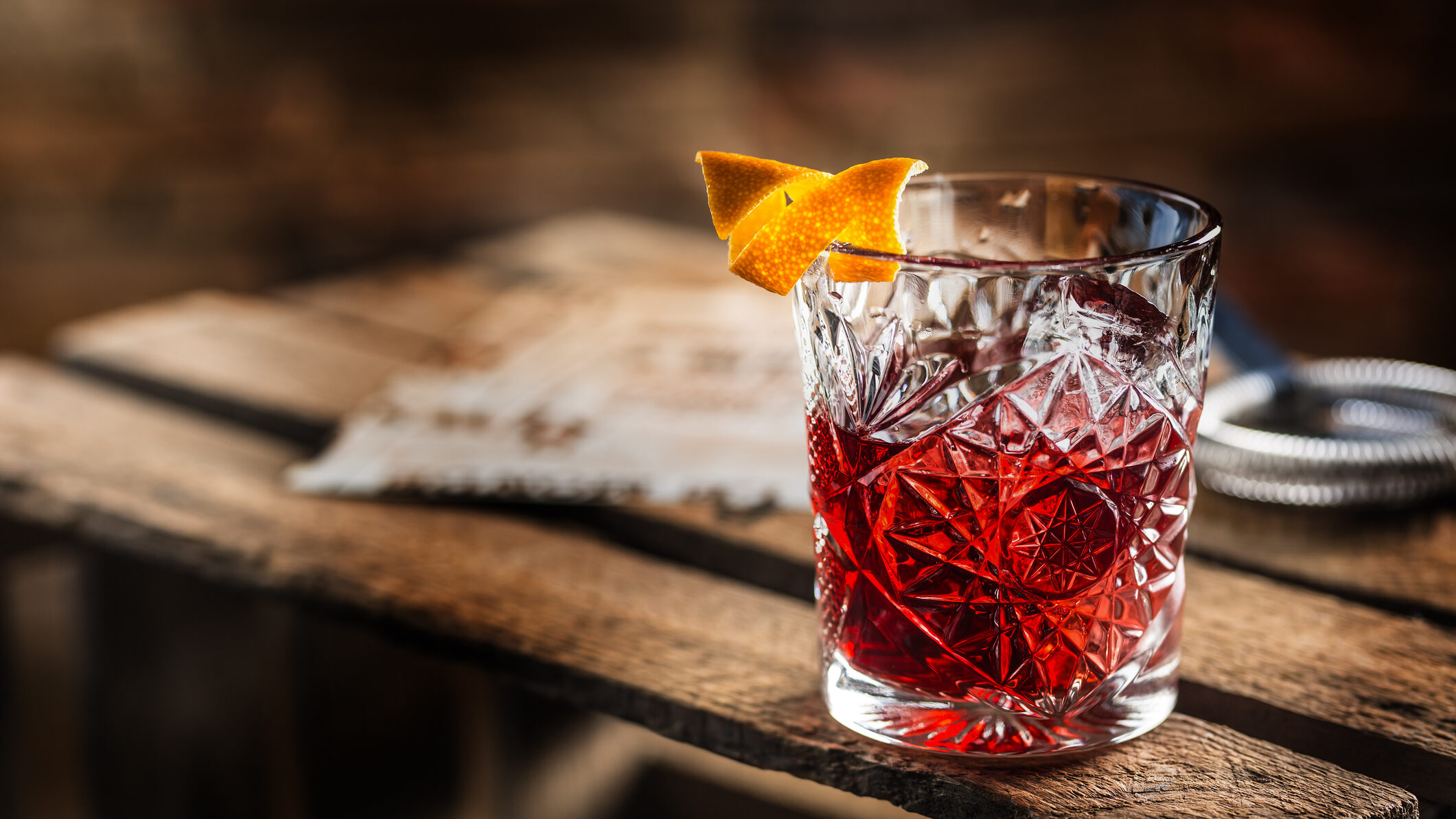 Ein Tumbler-Glas gefüllt mit Negroni und dekoriert mit Orangenschale steht auf einer Weinkiste aus Holz.