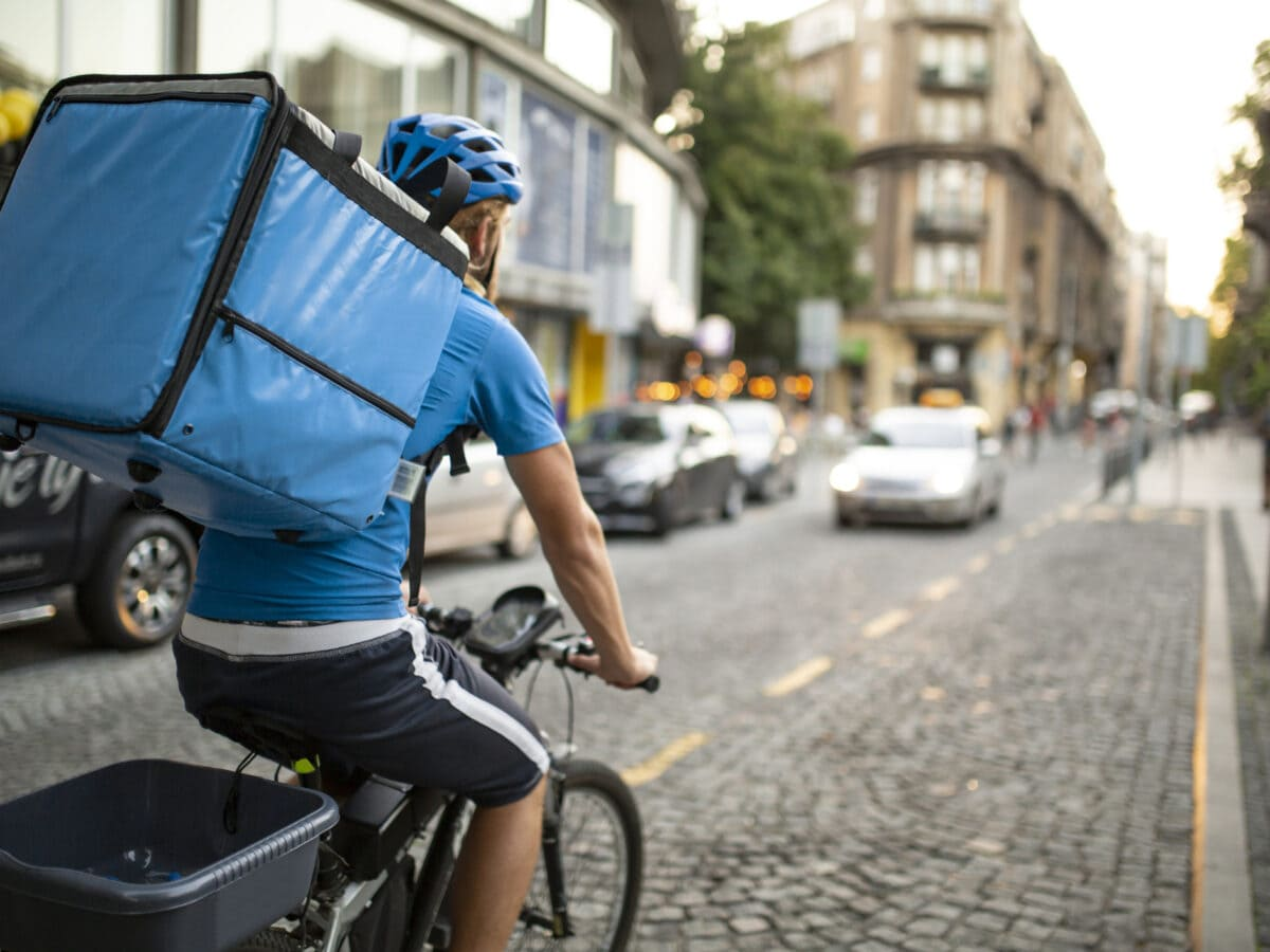 Wuplo: Ein Fahrradkurier, der von hinten zu sehen ist und einen großen Rucksack trägt, auf einer gepflasterten Straße.