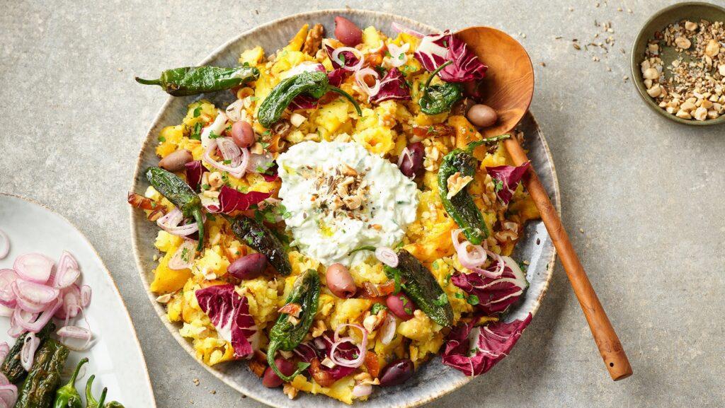 Der orientalische Stampfkartoffelsalat bunt auf einem großen Teller angerichtet. Im Hintergrund stehen Gewürze, Datteln, Jalapenos und Öl.