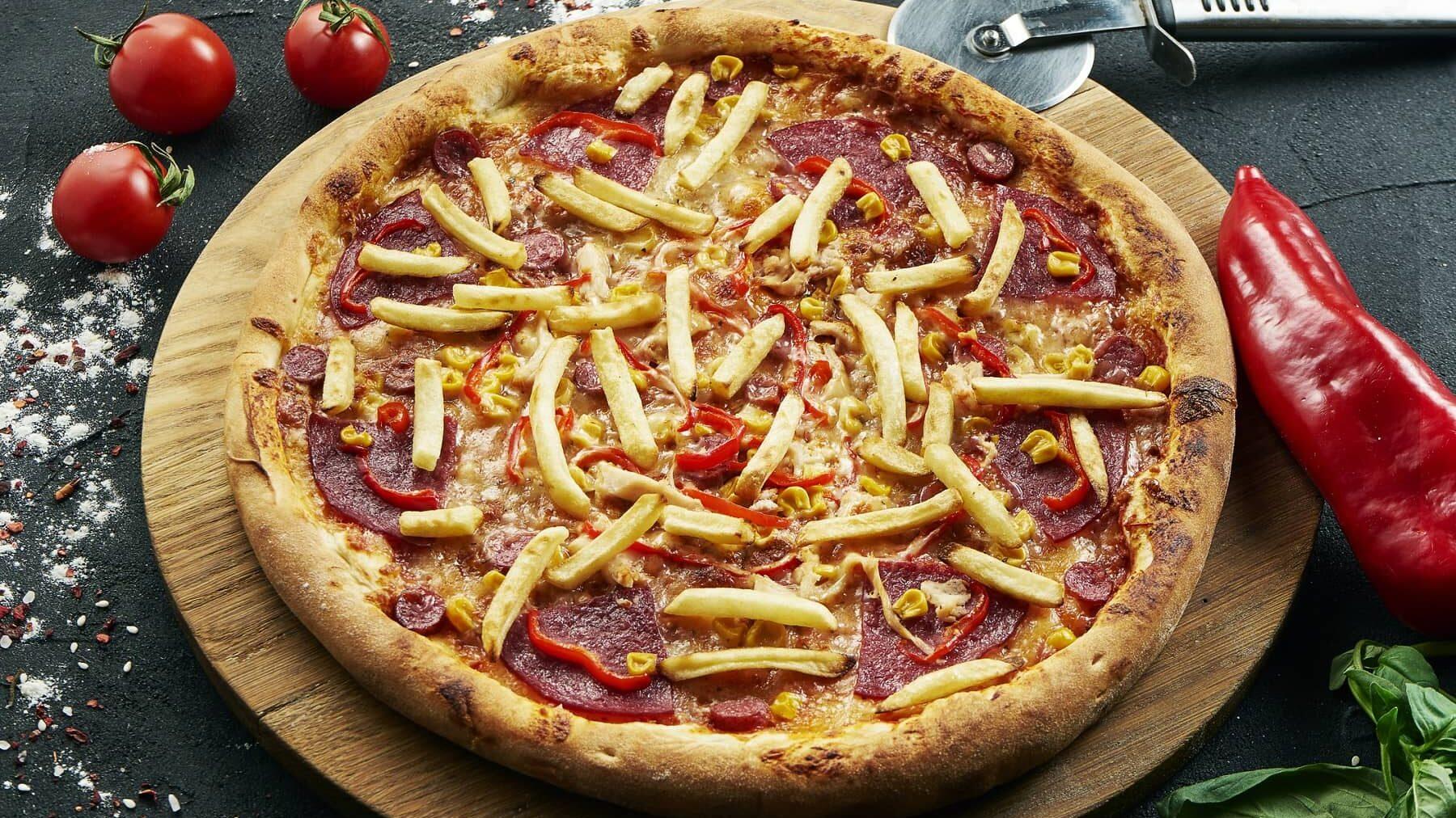 Eine Pommes-Pizza mit Salami-Paprika und Mais auf einem runden Holzbrett auf einem Steintisch. Um die Pizza herum liegen Paprika, Tomaten, ein Pizzaroller und Basilikum.