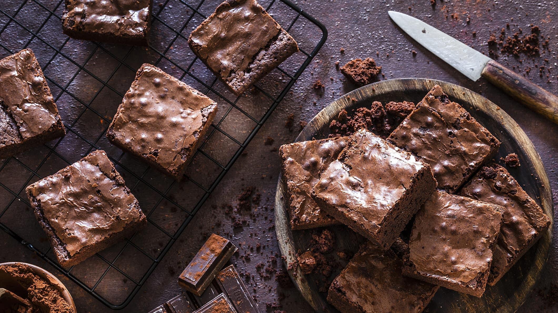 Ein Kuchengitter und rundes Holzbrett mit Süßkartoffel-Brownies in der Draufsicht. Daneben liegen ein Messer und Schokolade.