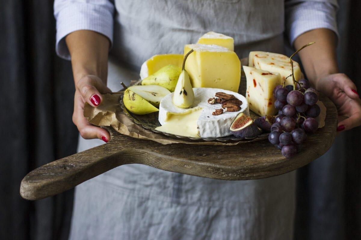 Was ist Lab? Eine Frau hält ein großes Holzbrett mit vielen verschiedenen Käse- und Obstsorten in den Händen.
