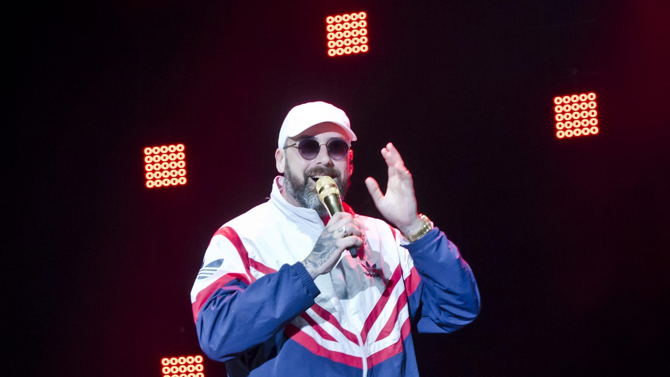 Rapper Sido mit Trainingsanzug, Kappe, Sonnenbrille und Mikrofon in der Hand auf der Bühne.