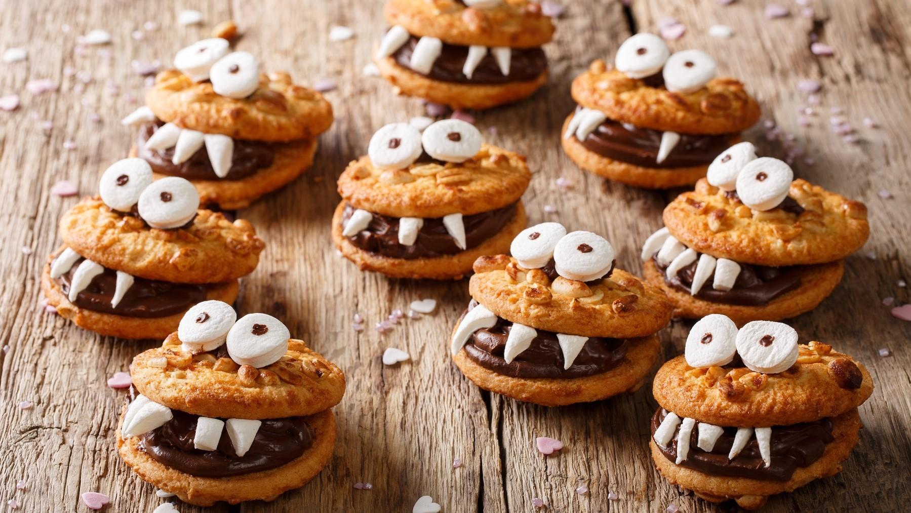 Mehrere Monster-kekse mit Marshmallow-Augen und Schokocreme liegen auf einem Holztisch. Um die Monster herum liegen Streusel in Herzform.