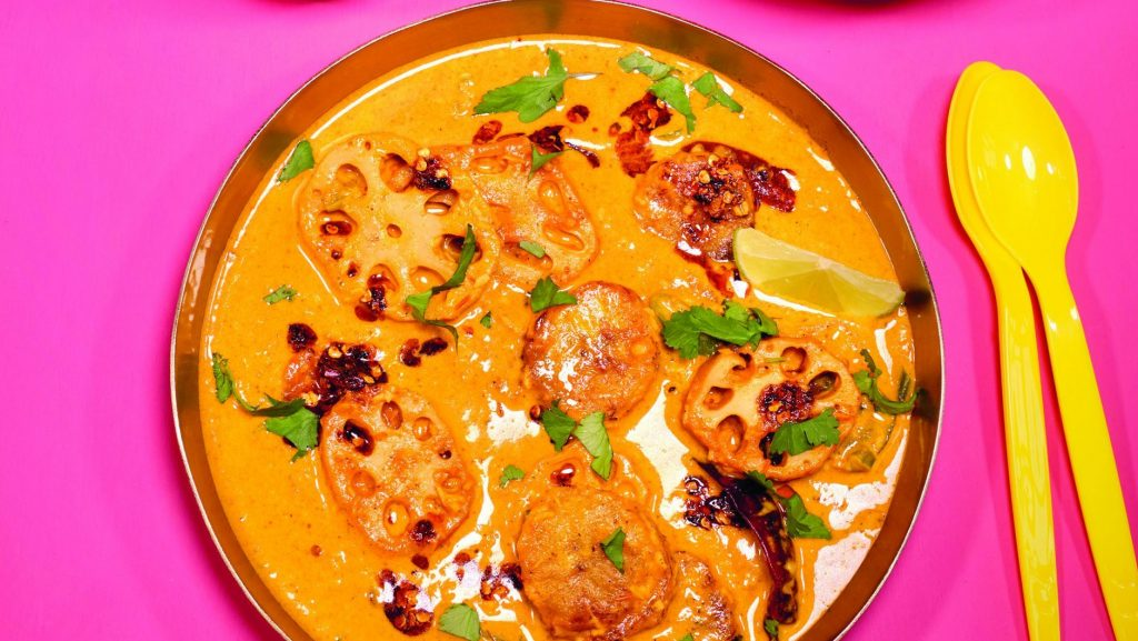 Das Lotuswurzel-Curry angerichtet in einer Schale, dazu als Topping Kokosflocken, Limette und Chilis.