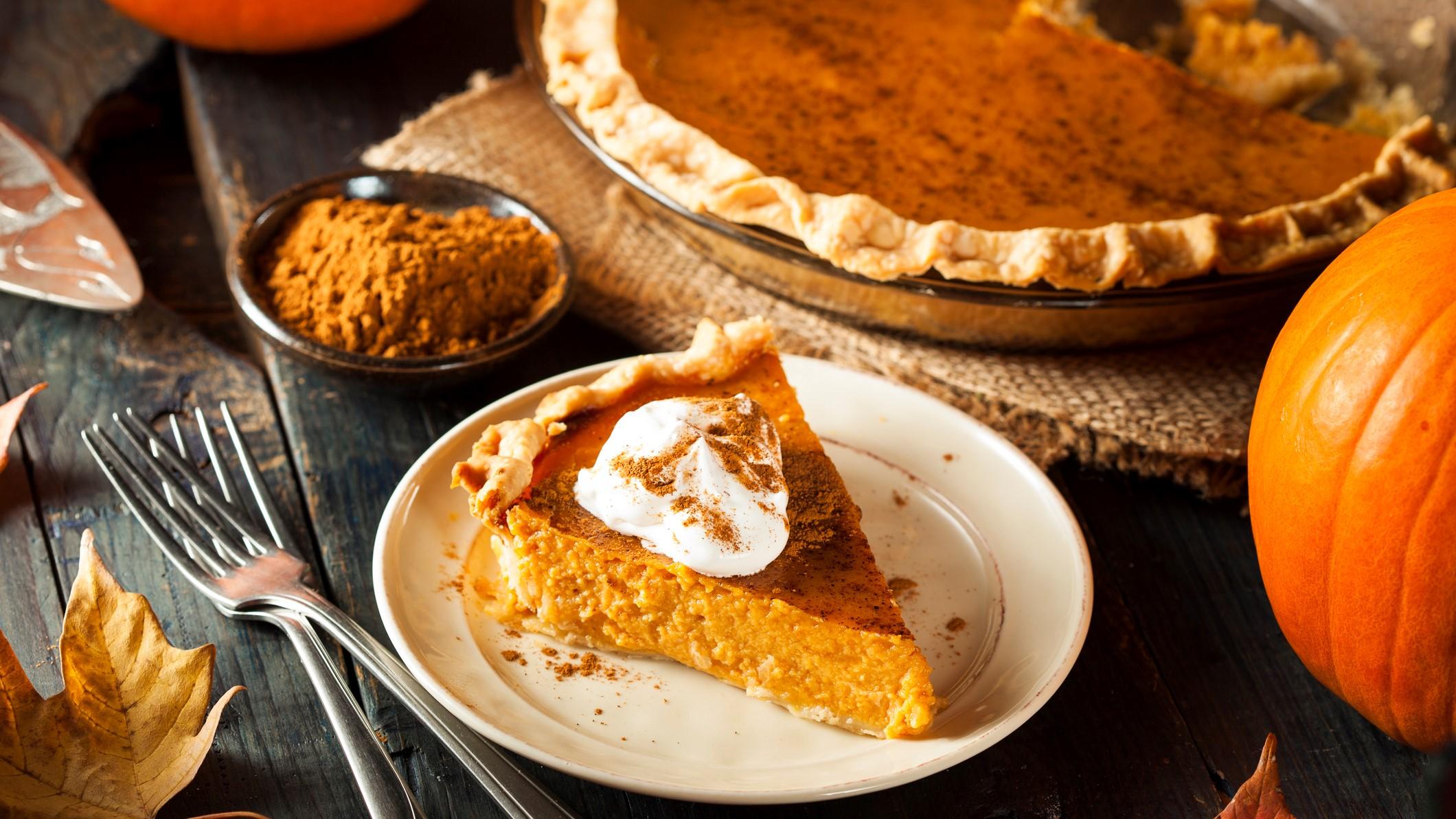 Angeschnittener Kürbiskuchen auf weißem Teller. Umgeben vom ganzen Kuchen und herbstlicher Dekoration.