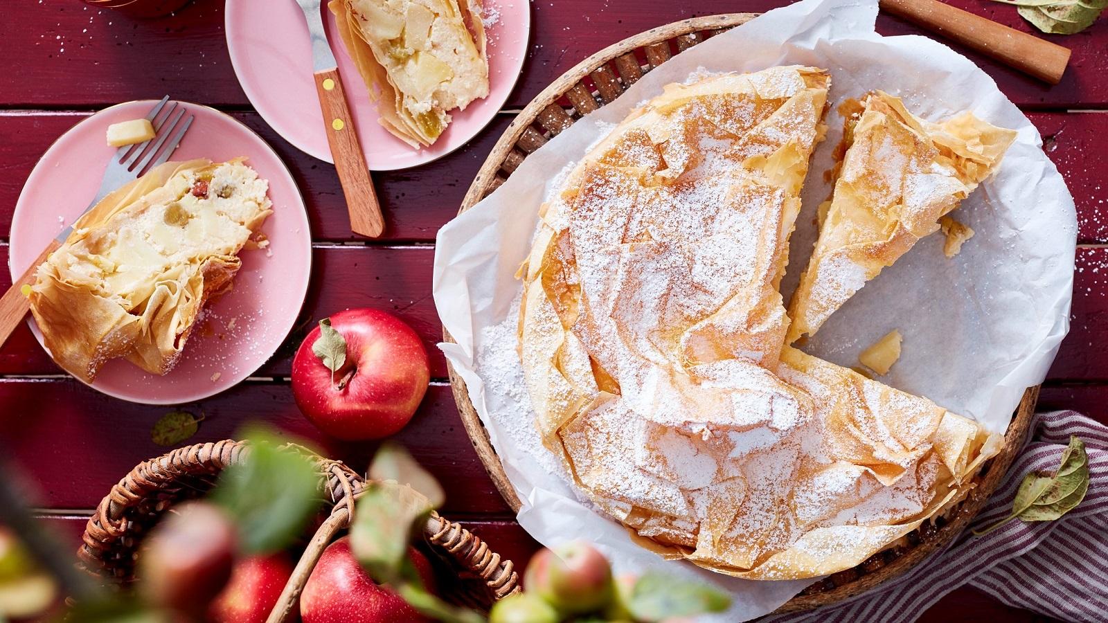 Ein angeschnittener Apfelstrudel-Kuchen auf einem weißen Backpapier neben zwei kleinen rosa Tellern mit jeweils einem Stück des Kuchens und einer Gabel, und frischen Äpfeln und einem Küchentuch, vor einem dunkel roten Holzhintergrund, von oben.