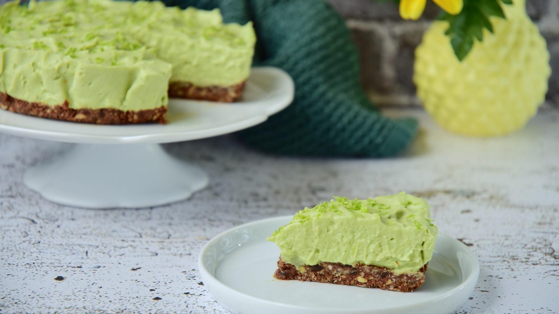 Ein Stück Avocado-Cheesecake mit Pistazien steht auf einem hellgrünen Teller auf einem gemusterten Untergrund. Im Hintergrund steht der restliche Kuchen auf einem Kuchentablett.