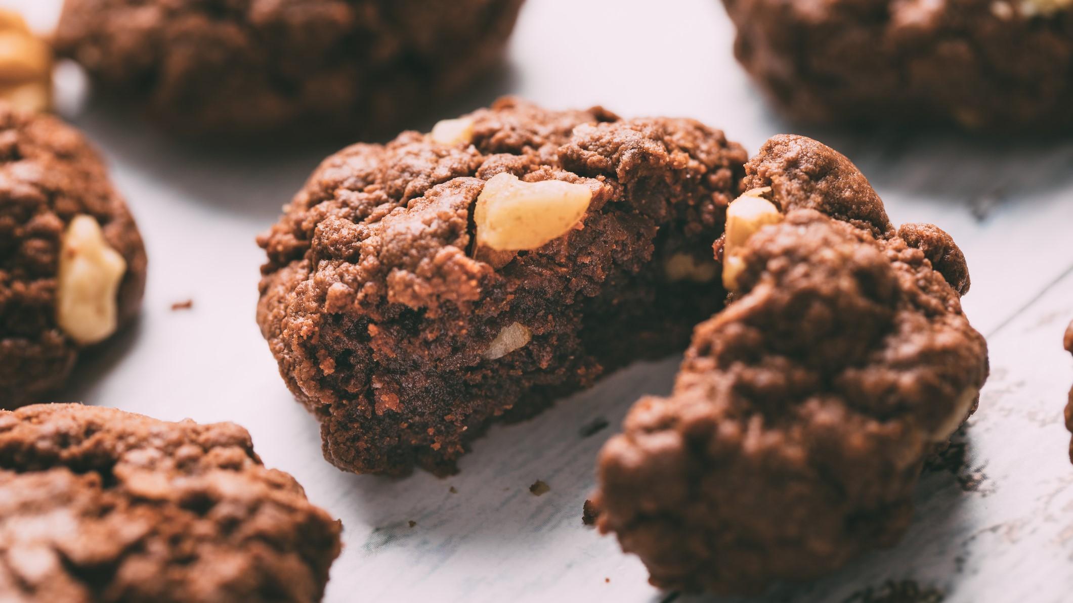 Ein angeschnittener Chocolate Chip Cookie mit dreierlei Schokolade auf hellem Holzuntergrund, drumherum sieht man unscharf ein paar weitere Kekse.