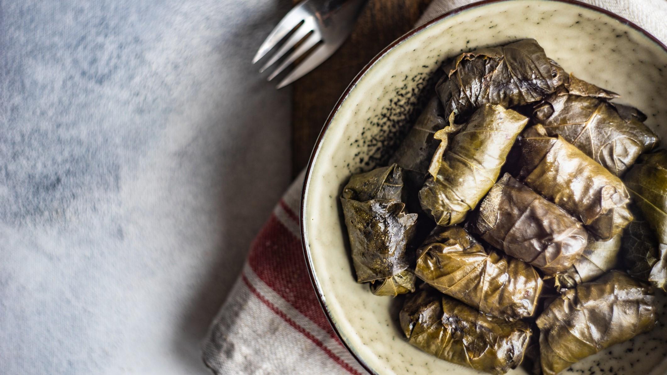 Ein Teller mit gefüllten Weinblättern auf einem Geschirrtuch in der Draufsicht, daneben liegt eine Gabel.