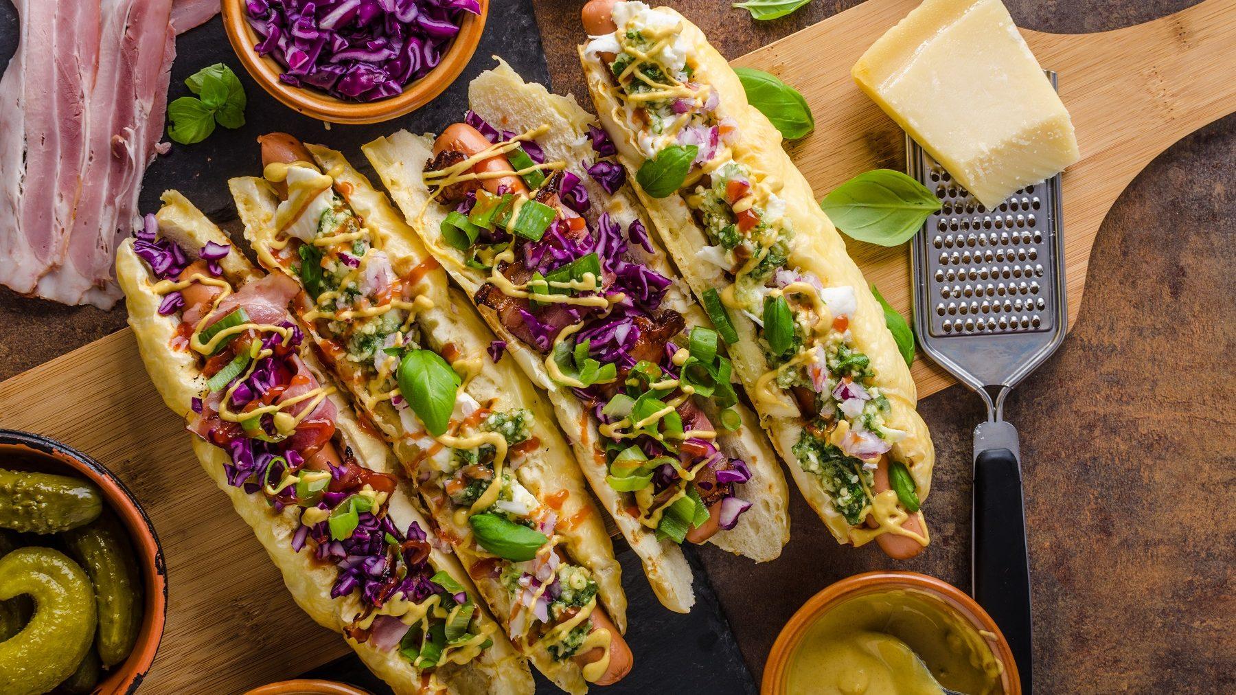 Hot Dogs mit Gemüse und Curry-Soße auf einem Holzbrett. Die Hot Dog Brötchen sind mit Käse überbacken. Um die Hot Dogs herum liegt bacon, vier Scalen mit Gurken, Lauch, Rotkohl und Curry-Soße. Rechts neben den Brötchen liegt ein Stück Käse mit einem Käsehobel. Über den Hot Dogs ist Basilikum verteilt.