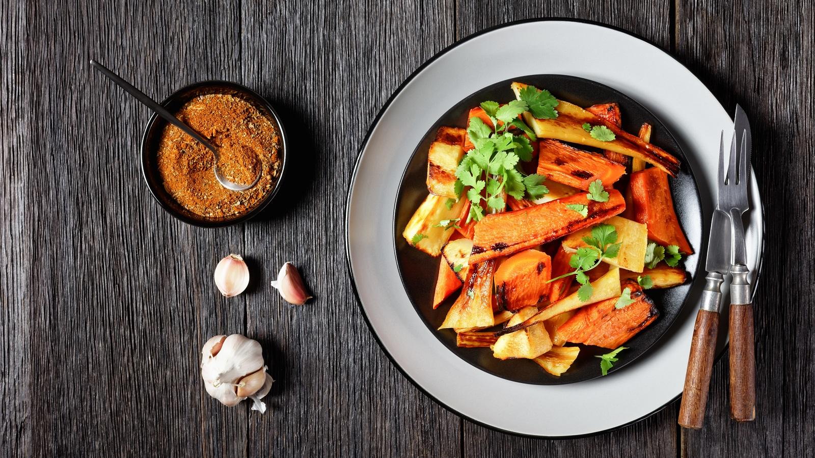 Ein Teller gefüllt mit gebackenen Karotten und Pastinaken, garniert mit frischem Koriander, neben einer Knoblauch-Knolle, einer kleinen Schüssel mit marokkanischen Gewürzen und Messer und Gabel, vor einem Holzhintergrund, von oben.