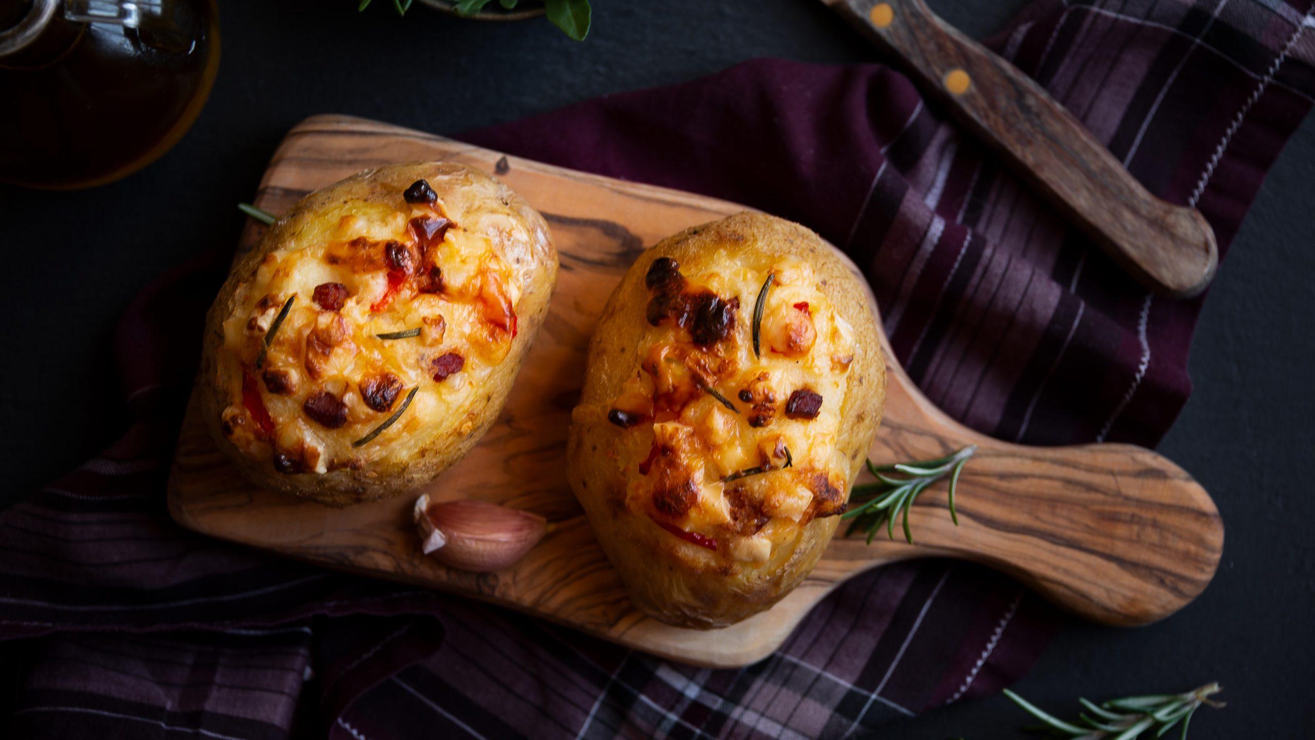 In der Draufsicht sieht man zwei gefüllte Kumpir mit Apfel, Paprika und viel Käse, die auf einem Küchenbrett liegen. Dunkler Untergrund mit einem Geschirrtuch.