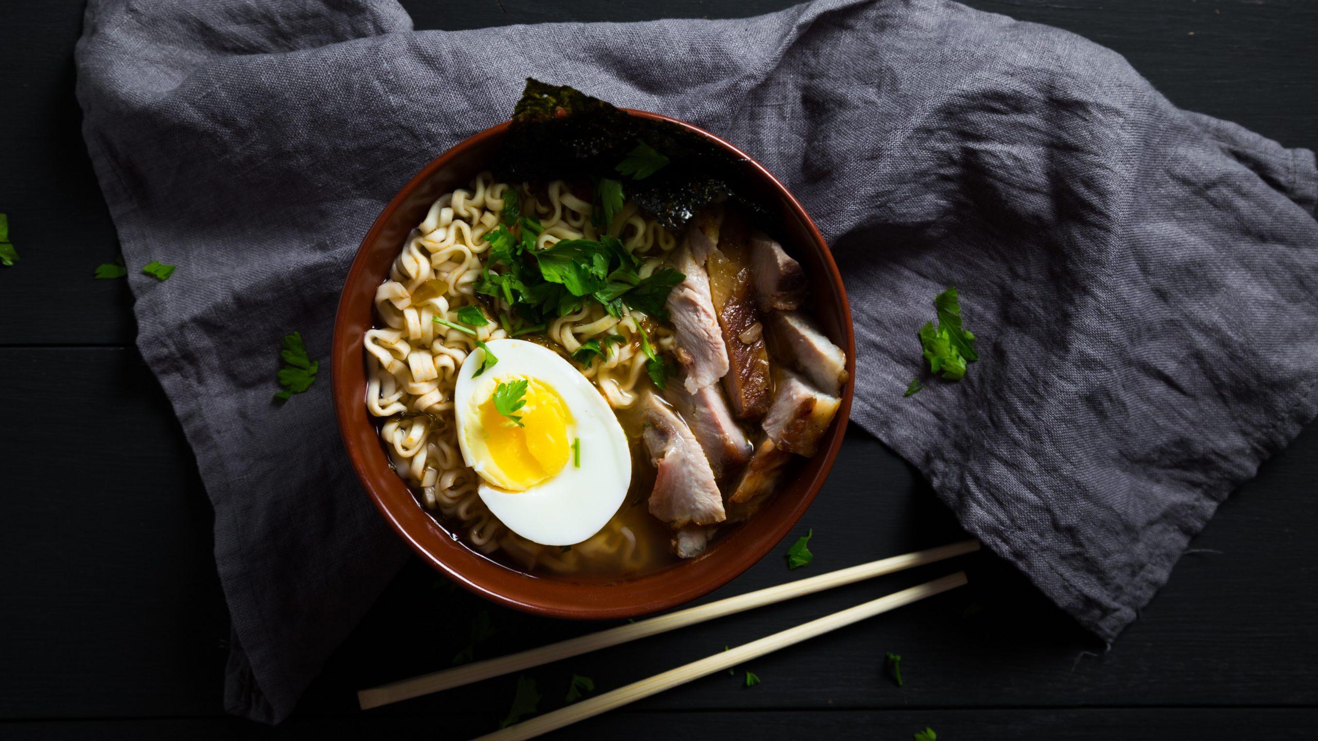 Eine Schüssel mit Miso Ramen mit eingelegtem Schweinebauch, einem halbem Ei, frischem Koriander und einem Noriblatt als Topping, neben einem Paar Essstäbchen, auf einem grauen Küchentuch, vor dunklem Hintergrund, von oben.