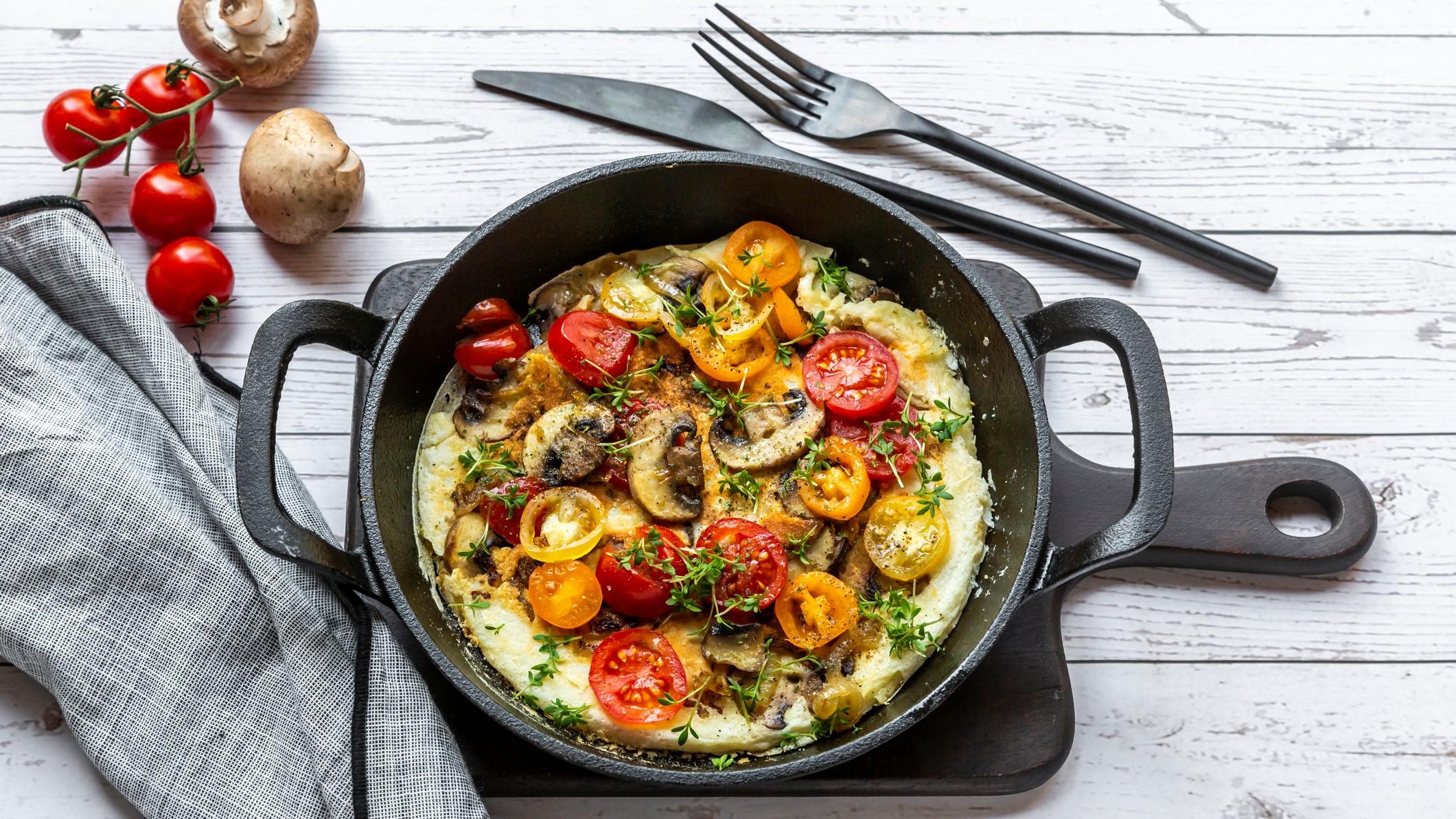 Eine gusseiserne Pfanne mit einem Omelett mit Pilzen und Tomaten sowie Oregano in der Draufsicht auf hellem Untergrund. Daneben liegen Besteck, ein paar Tomaten und Pilze sowie ein Geschirrtuch.