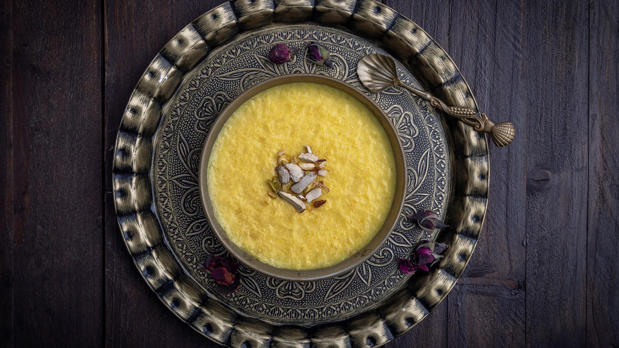 eine Schale mit persischem Reispudding, die auf einem verzierten Blechtablett steht, in der Draufsicht.