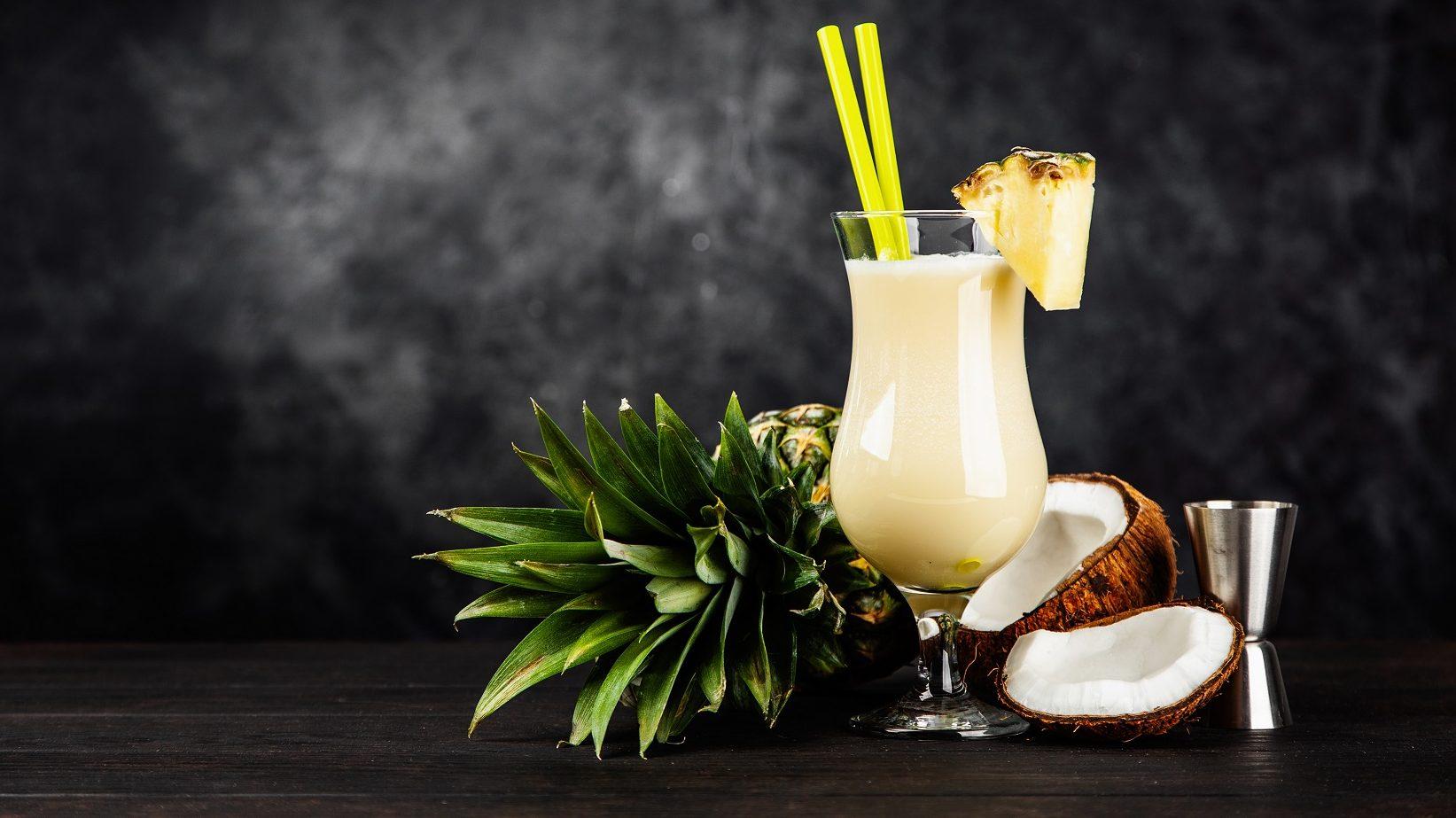 Die Low Carb-Pina Colada stilecht im Glas angerichtet, mit Ananas am Rand verziert und die Kokosnuss als Deko im Hintergrund.