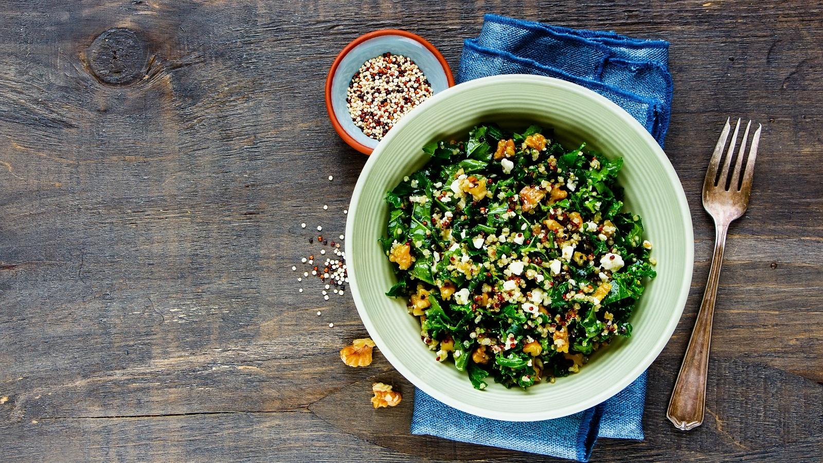 Eine hellgrüne Schüssel gefüllt mit dem Quinoa-Grünkohl-Salat garniert mit gerösteten Walnüssen und zerbröseltem Feta-Käse auf einem blauen Küchentuch neben einer kleinen Schüssel rohen Quinos-Körnern, zwei Walnüssstücken und einer Gabel vor einem Holzhintergrund, von oben.