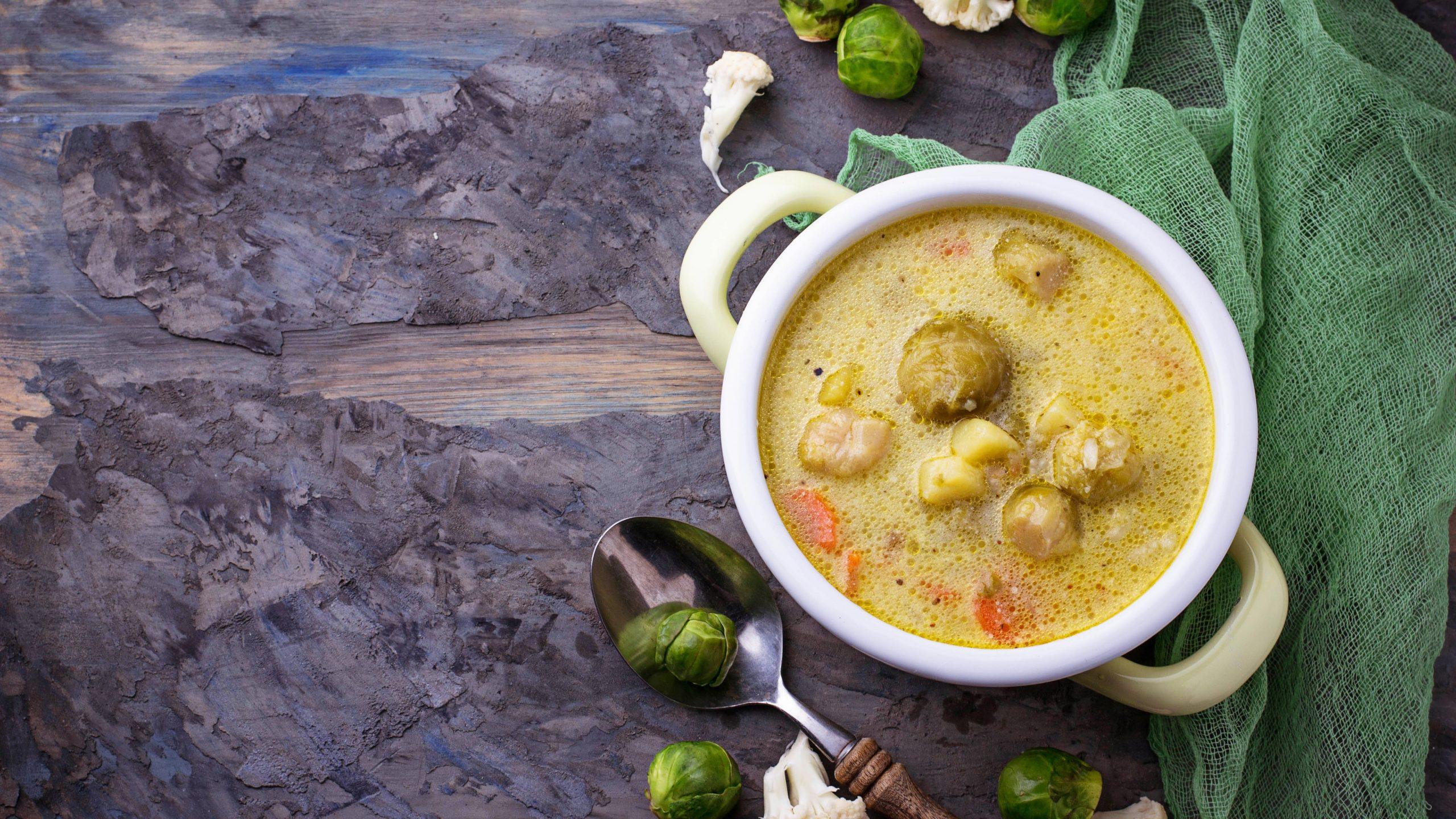 Eine Suppenterrine gefüllt mit Rosenkohleintopf mit Kartoffeln und Möhren auf dunklem Untergrund in der Draufsicht. Daneben lieben ein paar Zutaten.