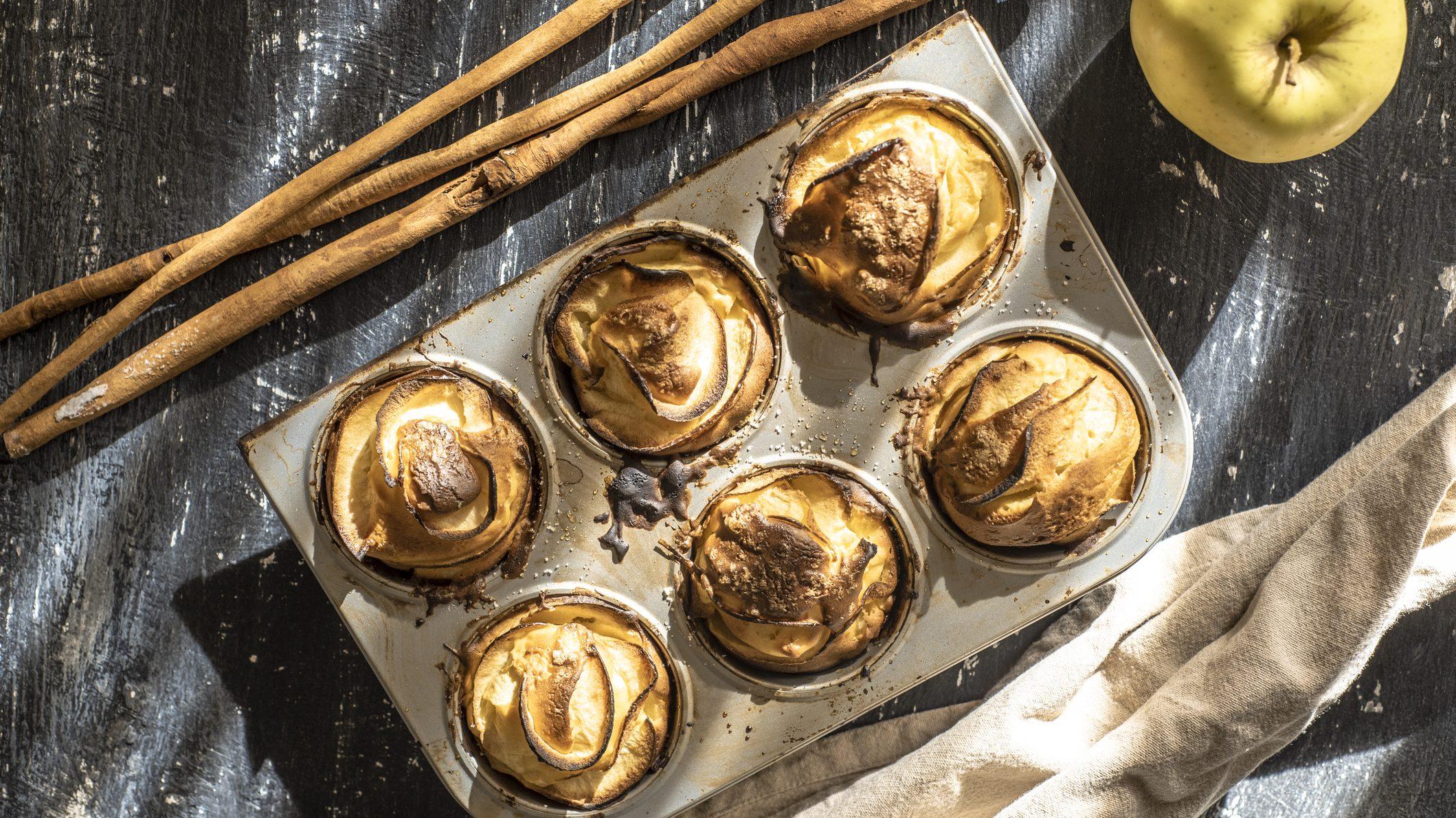 Auf einem dunklen Hintergrund ist eine Muffinform mit sechs saftigen Apfel-Muffins. Dabene liegen Zimtstangen und ein Apfel.