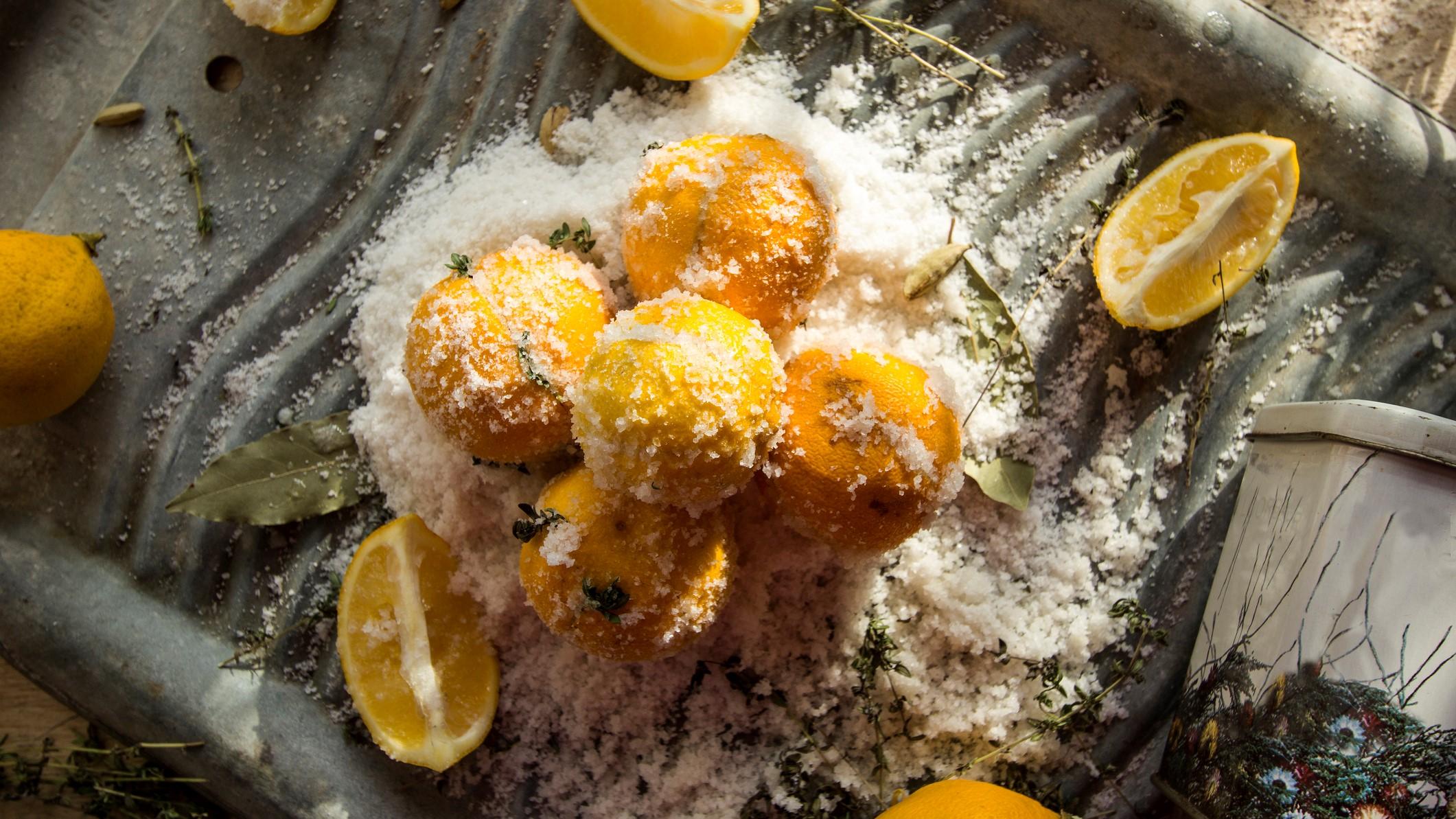 Auf einem gewellten Blech liegen ein paar Salzzitronen in einer Menge Salz.