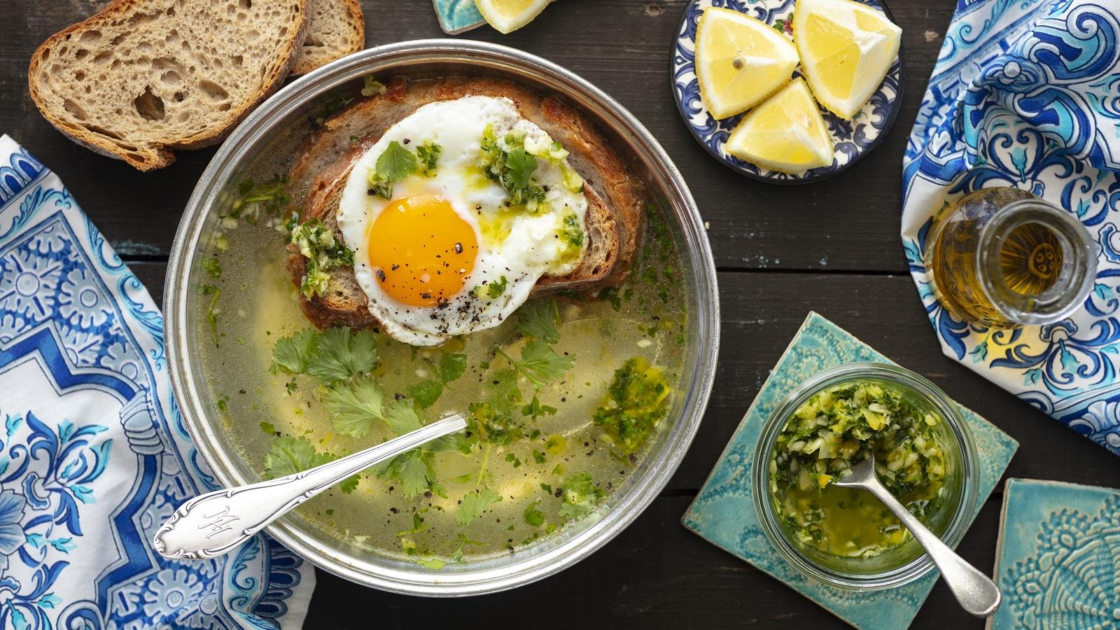 Eine Schüssel Sopa Alentejana neben einer kleinen Glasschüssel mit einer Knoblauch-Koriander-Paste, einer Karaffe mit Olivenöl, einem Teller mit Zitronenstücken und zwei Scheiben Brot, vor einem Holz-Hintergrund, von oben.
