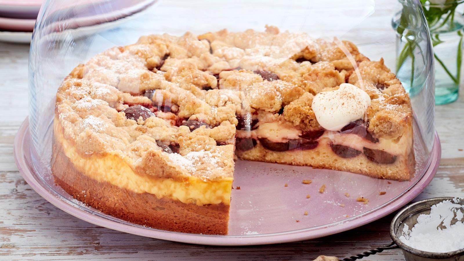 Ein angeschnittener Streuselkuchen mit Pflaumen und Zimt auf einem lila Teller bedeckt mit einer Glas-Glocke neben einer kleinen Schüssel Puderzucker vor einem hellen Hintergrund.