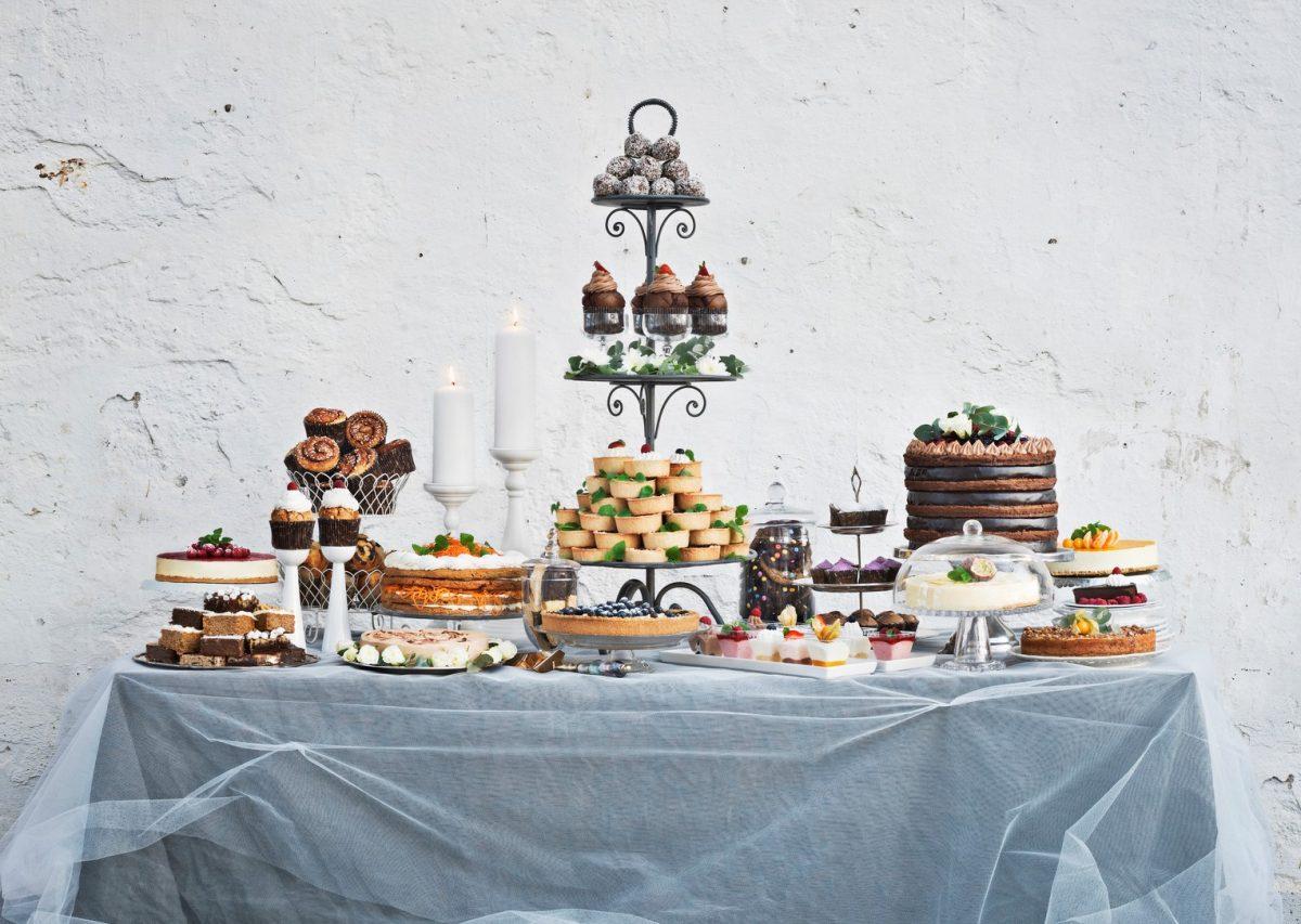 Ein Dessert-Buffet mit einer Vielzahl verschiedener Torten, Kuchen und Süßspeisen, aufgebaut auf einem Tisch.