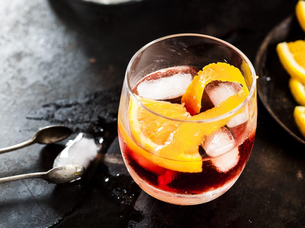 Ein Glas mit Negroni, Eiswürfeln und Orangenzeste auf dunklem Untergrund. Daneben liegen Eiswürfel, eine Eiswürfelzange und ein paar Zitronenscheiben auf einem Teller.