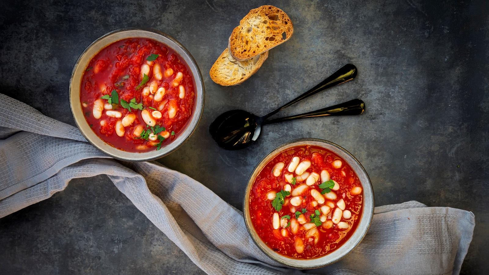 Zwei Schüsseln gefüllt mit jeweils einer Portion der tomatensuppe mit gerösteten Tomaten und Cannelli-Bohnen mit Petersilie garniert, neben zwei Löffeln, zwei Scheiben geröstetem Brot und einem Küchentuch, vor einem dunklen Hintergrund von oben.