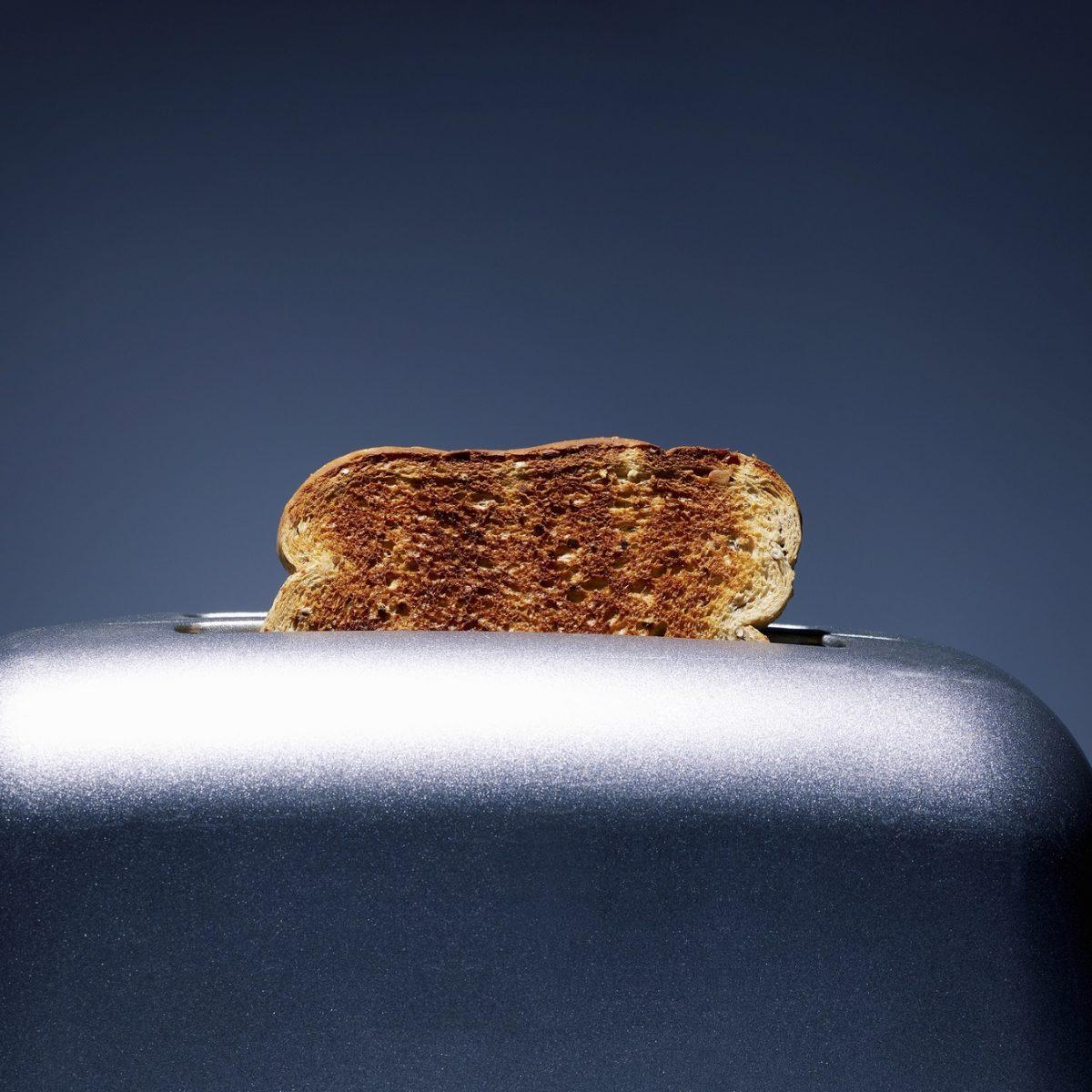 Woher kommt das Toastbrot? Ein Toast liegt geröstet in einem silbernen Toaster vor einem blau-grauen Hintergrund.